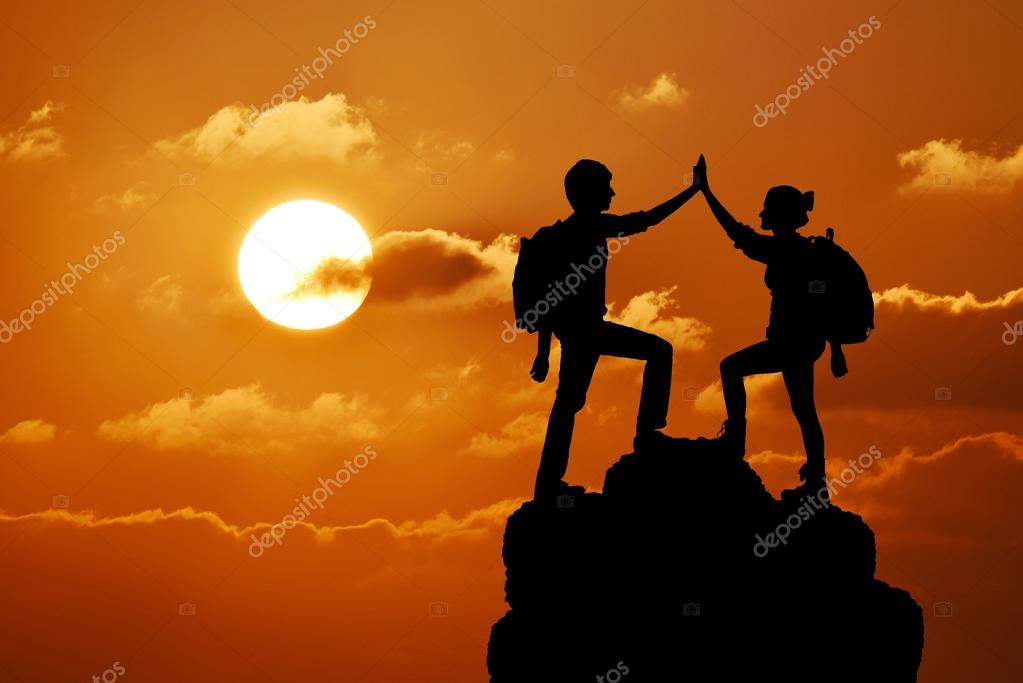 Silhouette of the two people man girl success on the peak of mountain. Sport and active life sunset landscape