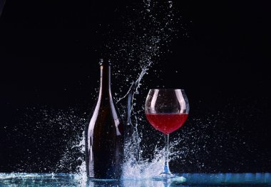 Bottle and glass with red wine, water splash, wine on table on dark black background, big splash around Glass and bottle of red wine splash on black