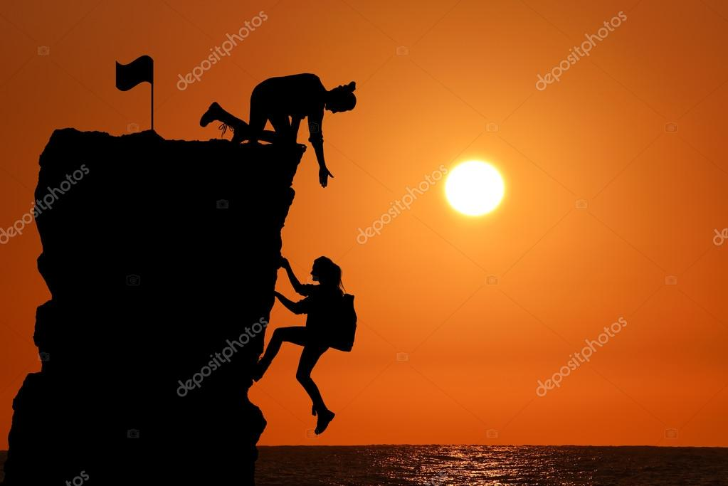 The joint work teamwork of two people man and girl travelers help each other on top of a mountain climbing team, a beautiful sunset landscape.