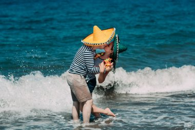a young couple kissing in the water at the beach in the Mexican