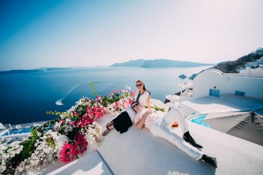 young couple embracing on the beach in Santorini, Greece.