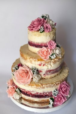 Wedding cake. Naked handmade cake rustic, decorated with roses.