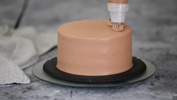 Séf díszítő csokoládé torta krémmel.