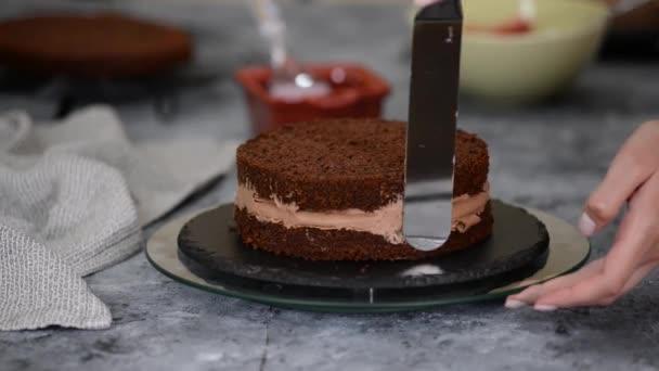 Detail ženy ruce dělat sladký třešňový dort s čokoládovou smetanou a sušenkou.