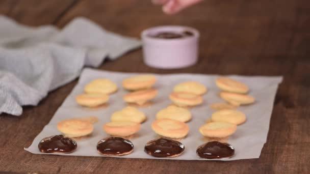 Ženské kuchařky zdobí sušenky s roztavenou čokoládou.