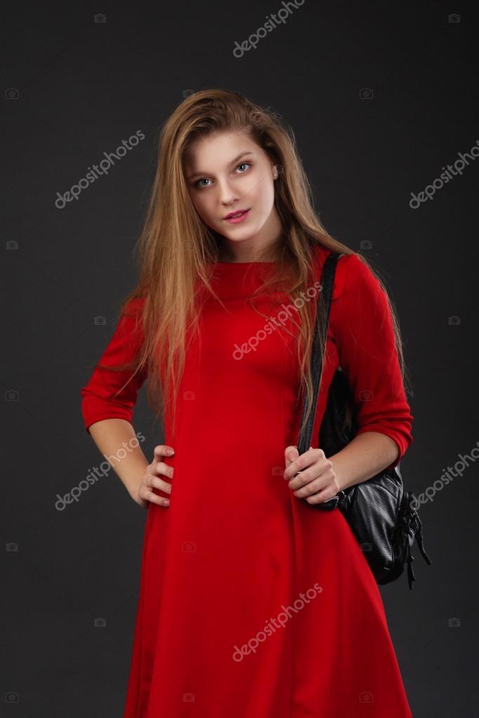 599bc73a051b33 Portret van een meisje in een rode jurk met een zwart lederen rugzak —  Stockfoto