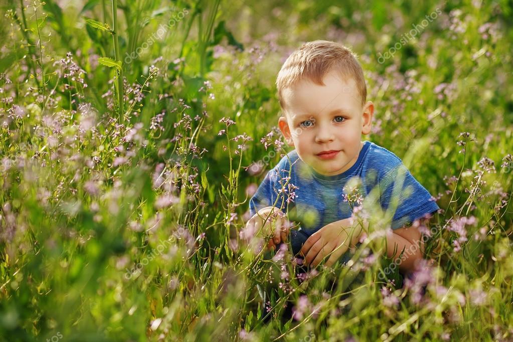 Beautiful little boy hiding in tall grass squatting
