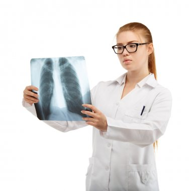Young beautiful woman doctor inspects an X-ray of the chest and
