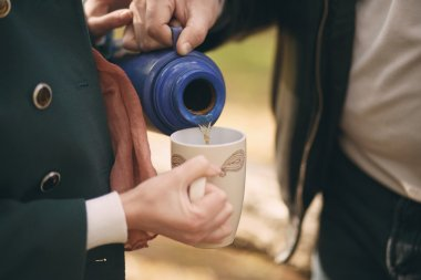 Couple pours tea from a thermos into the cup to warm up on the s