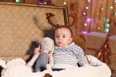 small boy sits in a suitcase with a toy in the room with Christm