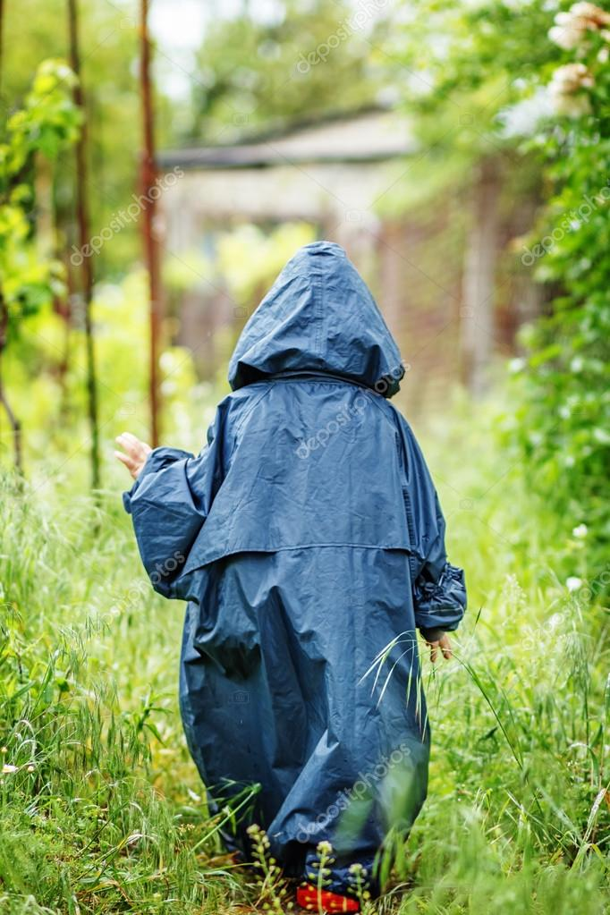 Funny little boy walks in the rain in a raincoat with a hood.