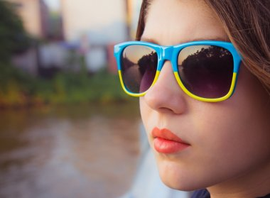 Portrait of a teenage girl in colorful sunglasses