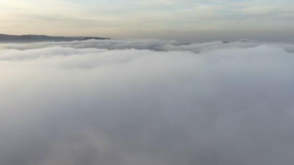 Letadlo nad bílými mraky. Hory na obzoru na pozadí malebné oblohy. Dron 4k. Pohled z ptačího pohledu