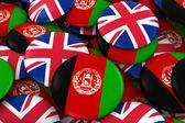 Fotografie Afghanistan and UK Badges Background - Pile of Afghan and British Flag Buttons 3D Illustration