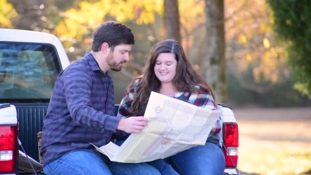 Couple Planning Trip on the Back of a Pick-up with map