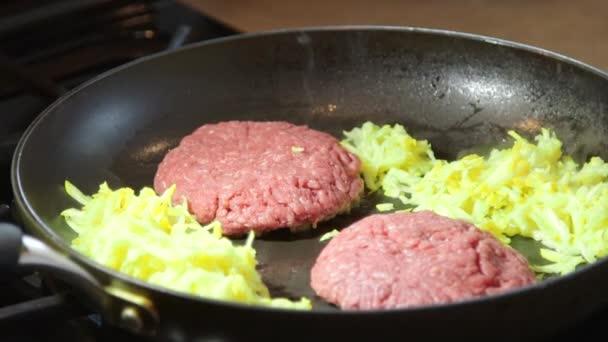 cucinare hamburger di carne macinato di manzo in padella calda su piano cottura video stock