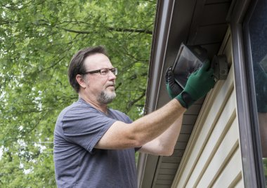 Electrician Working On Exterior Light
