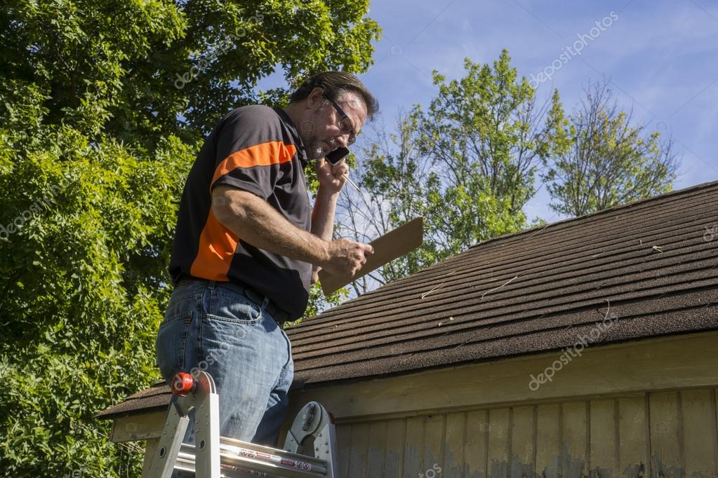 Contractor On Ladder Figuring Hail Damage Repairs To Roof