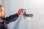 Der Elektriker grundiert die Löcher und Kanäle für Steckdosen und Drähte.