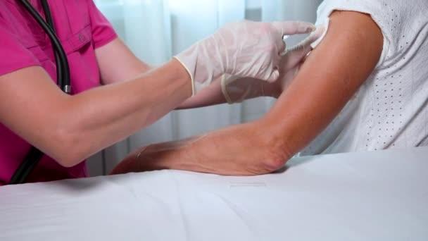 Eine Ärztin in weißen Handschuhen macht eine Impfung, eine Impfung gegen Coronavirus, Grippe.