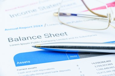 Blue ballpoint pen on a corporate balance sheet with eye glasses.
