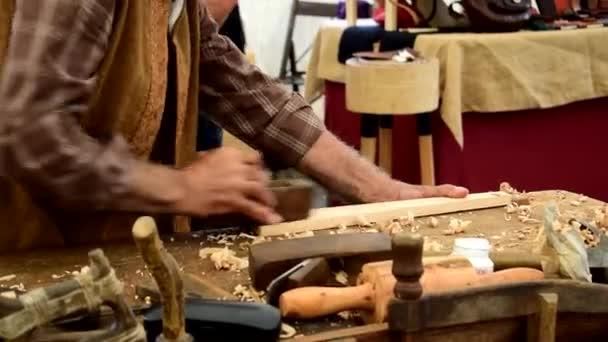 Tischler schleift Holz mit einer Hobelmaschine auf einer Handwerksmesse in Galicien, Spanien