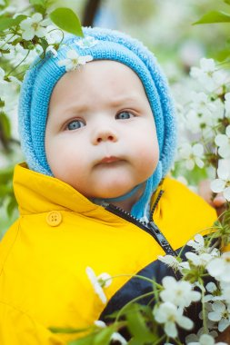 Cute little baby in blue hat over spring blossom trees
