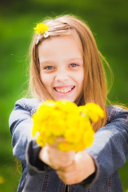 Portrait of smiling young girl holding bouquet of flowers