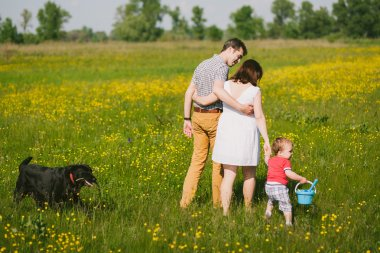 Happy family walking with black labrador dog in summer field