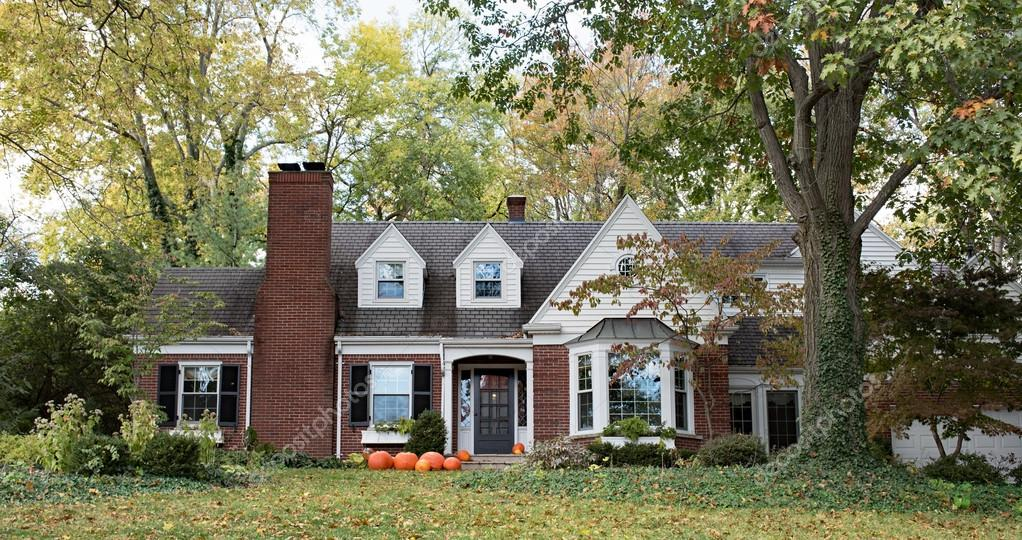 Red Brick House in Wooded Setting with Pumpkins
