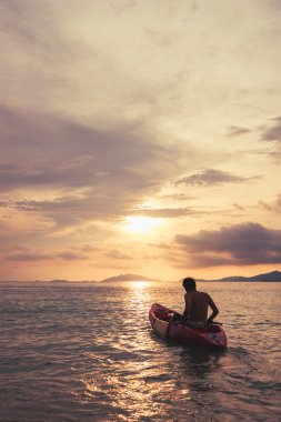 a guy on kayak boating to sunset, vintage tone, abstract concept