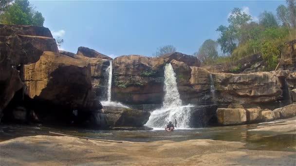 Man meditiert in einem Wasserfall