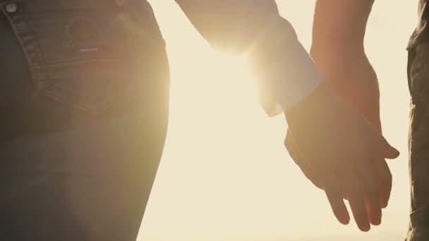 A férfiak és nők a naplemente kezek