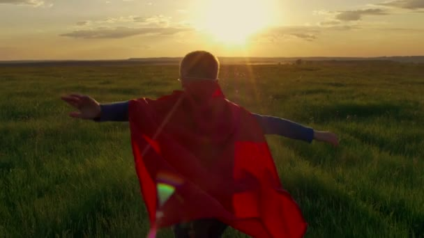 supereroe del ragazzo in un campo al tramonto