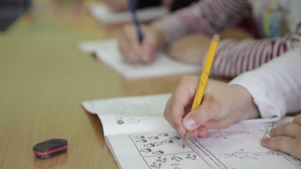children write in a notebook in kindergarten