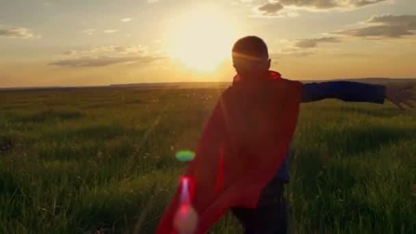 Fiú öltözött a Superman köpeny futás-ban egy mező a naplementébe keres