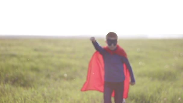 chlapec superhrdina v poli při západu slunce