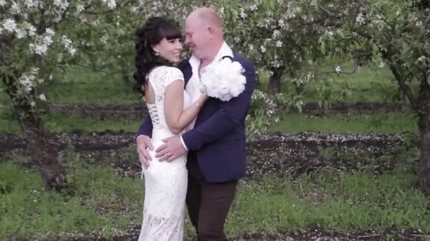 Nevěsta a ženich romantickou procházku v jabloňový sad