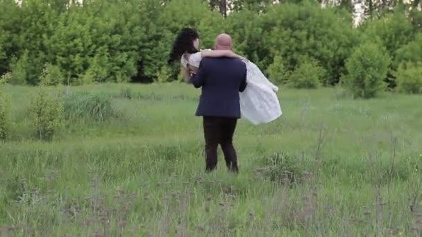 ženich svou nevěstu drží v náručí