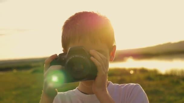 Junge fotografiert seine Mutter, die abends bei Sonnenuntergang am Seeufer steht
