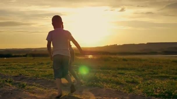 zwei glückliche Kinder, die im Park herumlaufen und springen. Auf dem Feld spielen die beiden Brüder bei Sonnenuntergang
