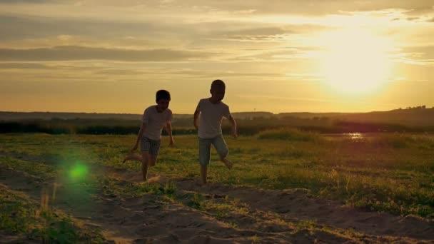 Dvě šťastné dítě běhat a skákat v parku. Na hřišti oba bratři hrají při západu slunce