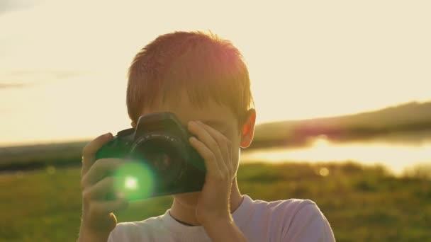Chlapec fotografování jeho matka, stojící na břehu jezera v večer při západu slunce