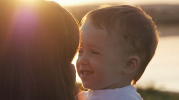 At the evening time before the sunset, baby feeling happy and smiles with her mother in the garden