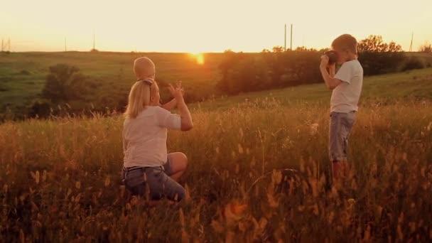 Rodina je fotografoval v poli při západu slunce. Matka a dva syny na dovolené činí selfie
