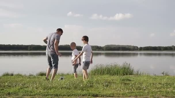 Father and two son playing football on the beach at the day time. Concept of friendly family.