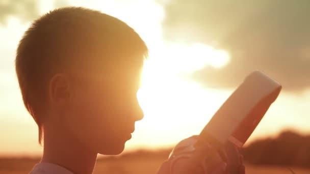 Ten kluk má sluchátka v poli při západu slunce