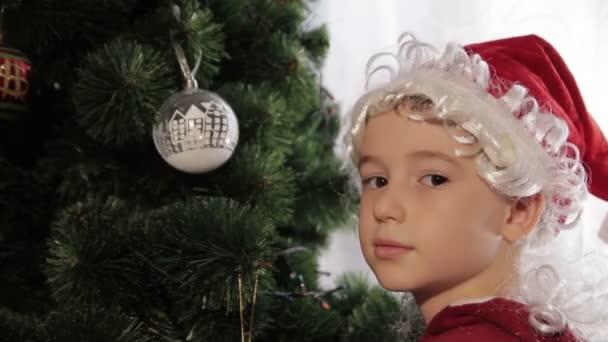 Küçük çocuk annesi Noel ağacı süslemek için yardım.