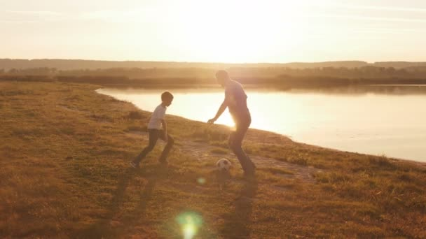 Young family frolicked together to play football football on the beach at sunset