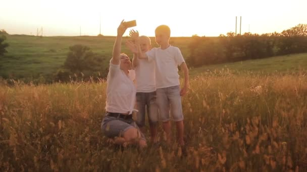 Family is photographed in a field at sunset. Mother and two sons on vacation make selfie